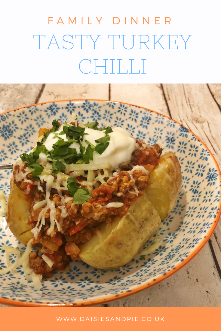 "homemade turkey chilli loaded into baked potatoes and topped with soured cream and grated cheese. Text overlay saying ""family dinner tasty turkey chilli"""