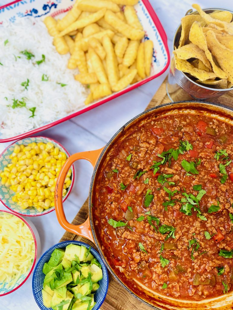 turkey mince chilli served with side dishes of chips, rice, sweetcorn, grated cheese and chopped avocado
