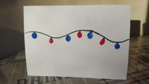 homemade Christmas card with chain of fairy lights across the card
