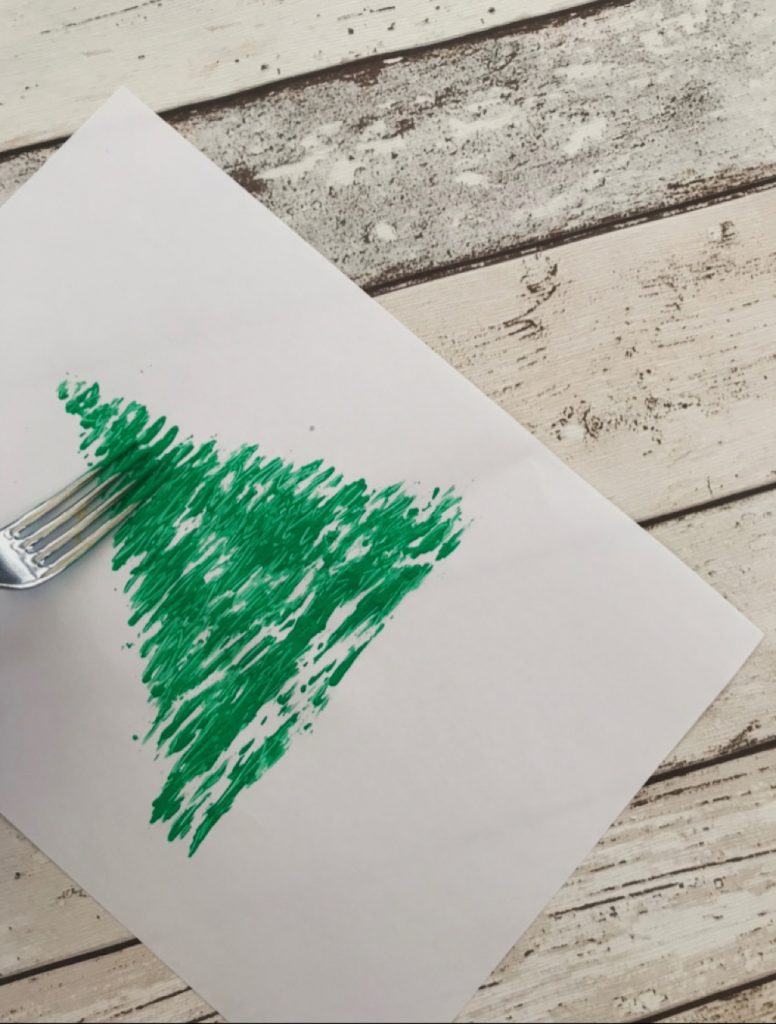 using a fork to paint a Christmas tree with green paint