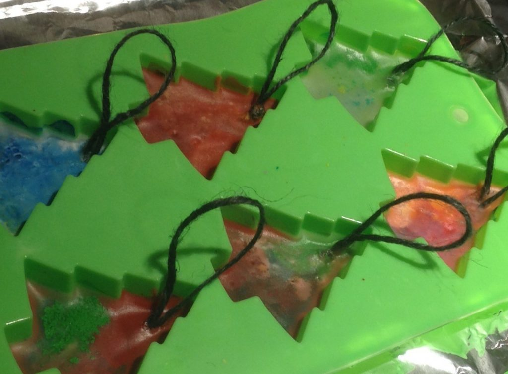 green Christmas tree mould filled with melted wax crayons