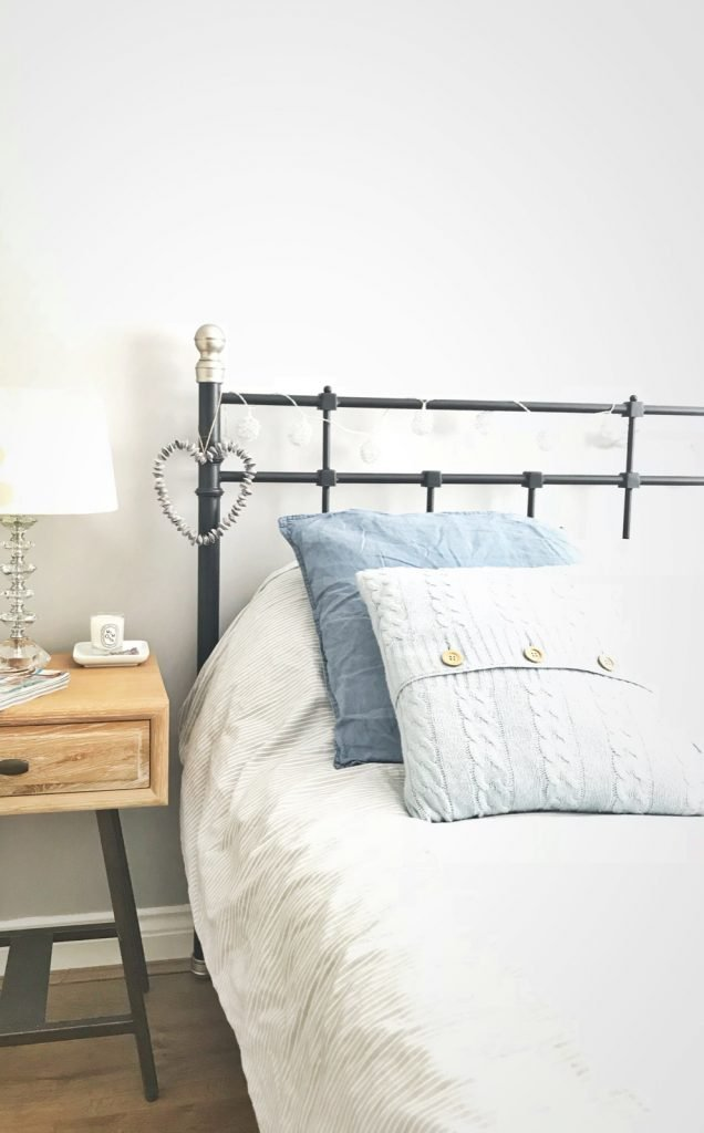 cast iron bedstead made up with pale grey striped duvet and pale blue woollen pillows, purple shell heart hanging from the bed post. - next to the bed is an oak bedside table from Loaf with a white and blue spotted lamp from Laura Ashley alongside a Diptyque mimosa canldle