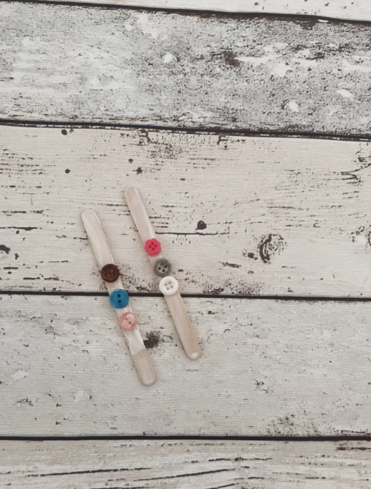 lollipop sticks with buttons stuck on them ready to make a snowman