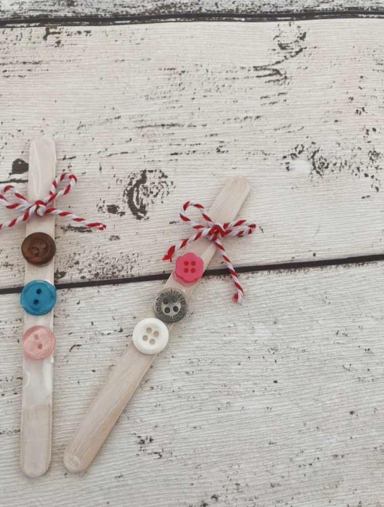 lollipop sticks with buttons and string tied on ready to be made into snowman
