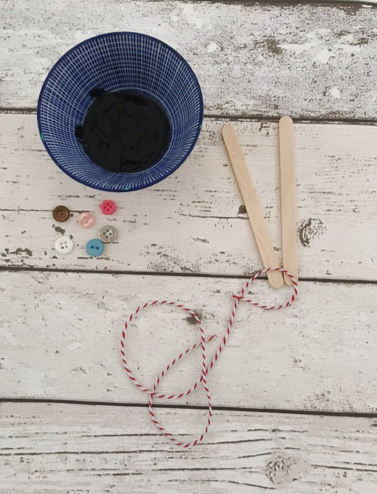 bowl of black paint, lollipop sticks, string and buttons ready to make a snowman