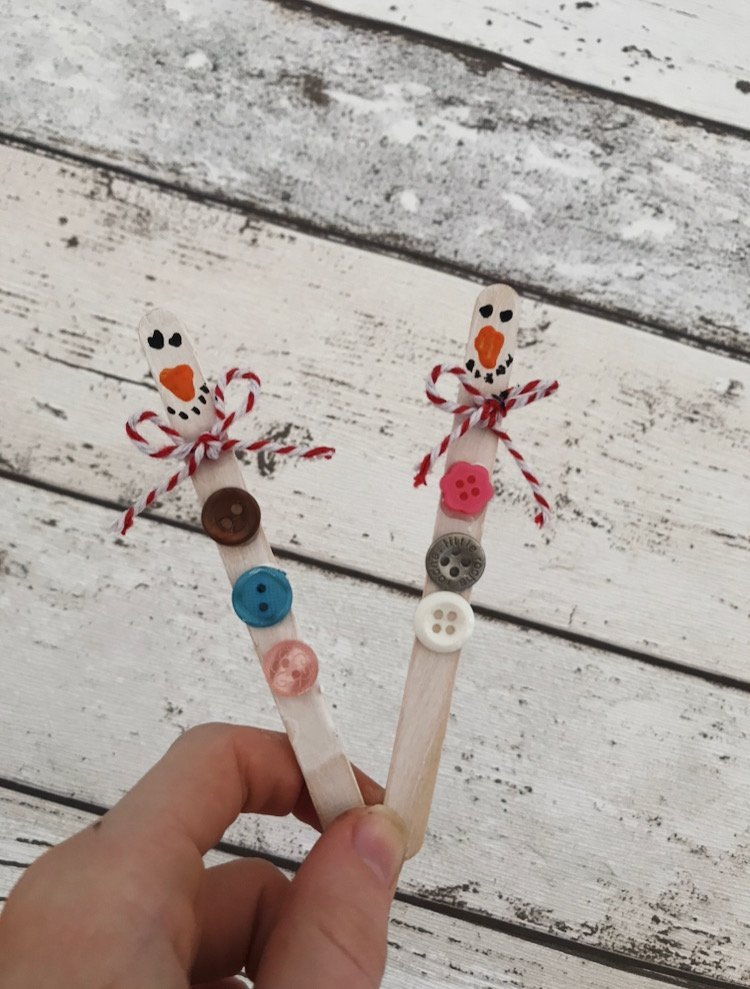 lollipop sticks with buttons and string and a little face painted on them ready to be made into snowman