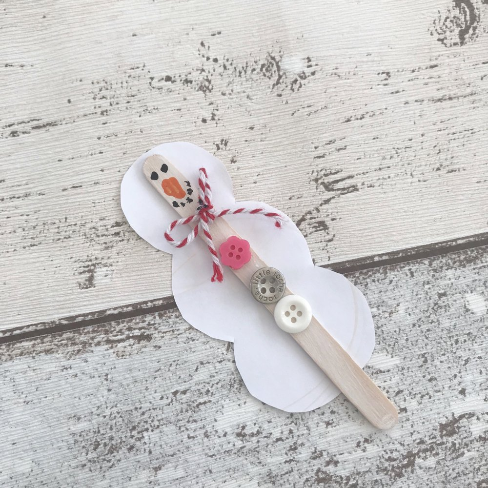 snowman made from a popsicle stick and buttons with a red and white string scarf tied around neck.