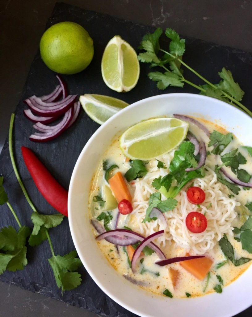 bowl of vegan thai coconut curry with noodles on a black table with fresh lime wedges, red chillies and coriander