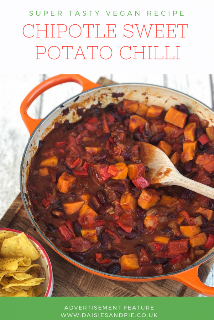 """Orange Le Creuset pan filled with homemade vegan chipotle sweet potato chilli served with a bowl of nacho crisps. Text overlay saying """"Super tasty vegan recipe - chipotle sweet potato chilli"""""""