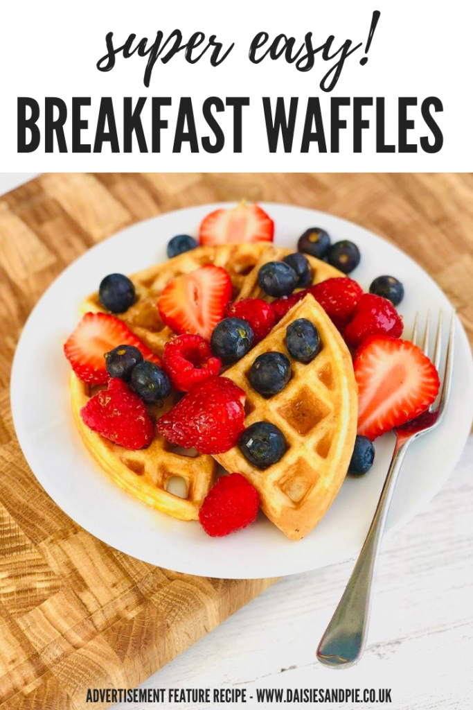 "easy breakfast waffles topped with strawberries, blueberries and raspberries, drizzled with maple syrup. Waffles served on a white plate with silver fork. Text overlay ""super easy breakfast waffles - advertisement feature recipe www.daisiesandpie.co.uk"""