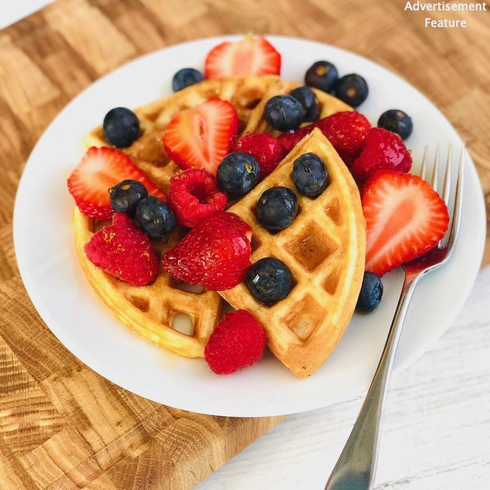 easy breakfast waffles topped with strawberries, blueberries and raspberries, drizzled with maple syrup. Waffles served on a white plate with silver fork