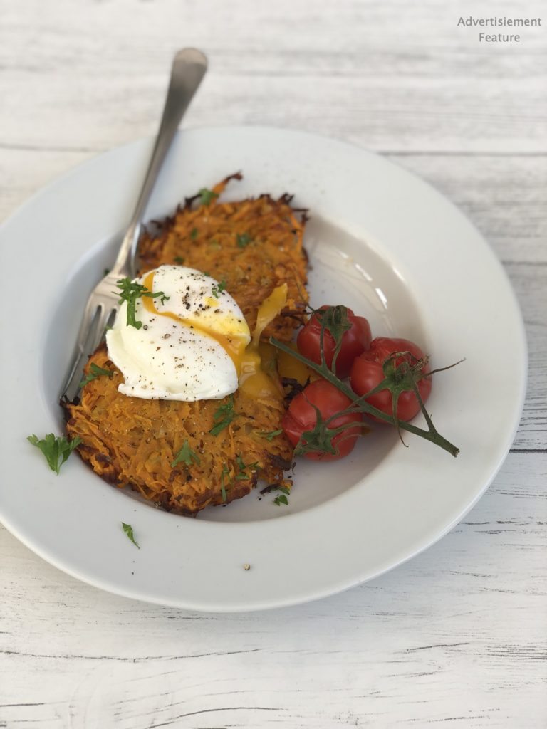 two homemade sweet potato rosti topped with poached egg served alongside oven blistered vine tomatoes