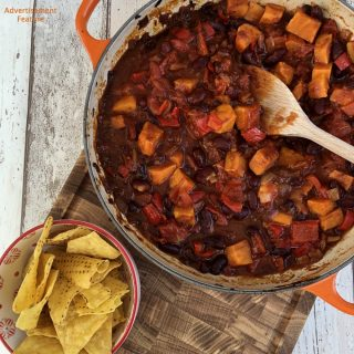 Orange Le Creuset pan filled with homemade vegan chipotle sweet potato chilli served with a bowl of nacho crisps