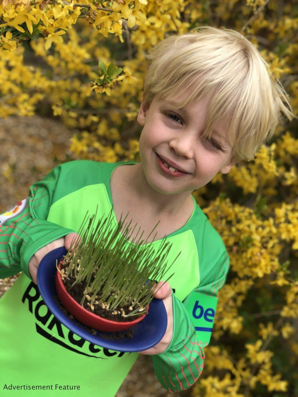 Mud & Bloom kids subscription box - boy holding wheatgrass he's grown