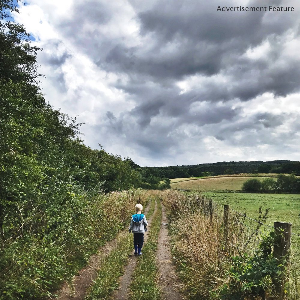Mud & Bloom kids subscription box - boy walking through fields to woodland on a nature trail