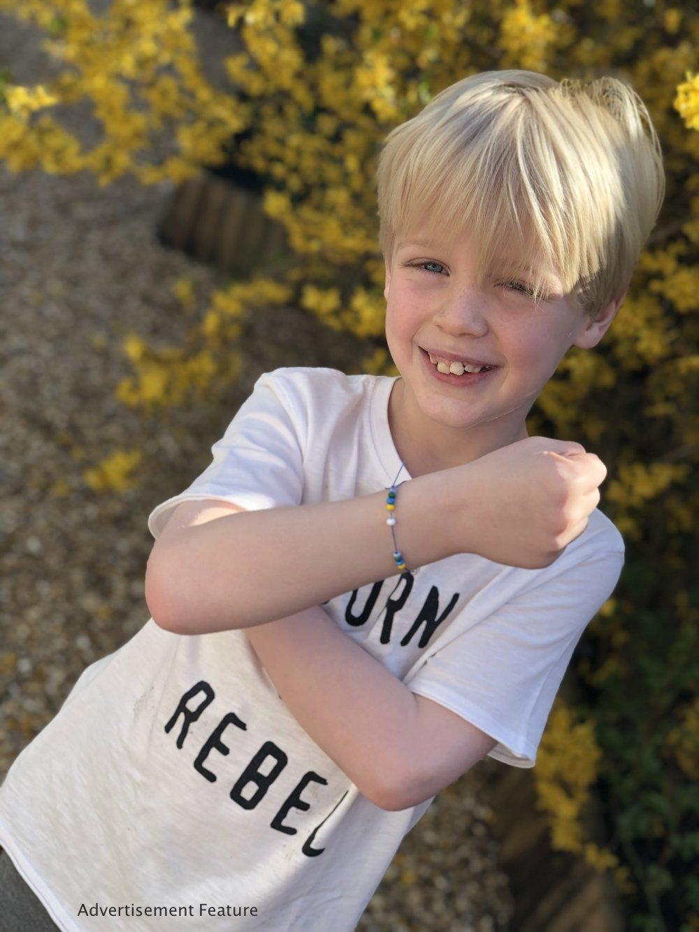 Mud & Bloom kids subscription box - boy showing off the water cycle bracelet he's made