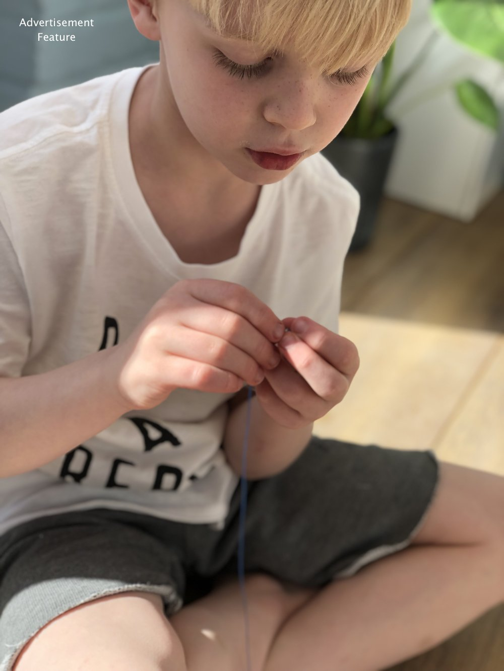 Mud & Bloom kids subscription box - boy threading beads onto the water cycle bracelet he's making