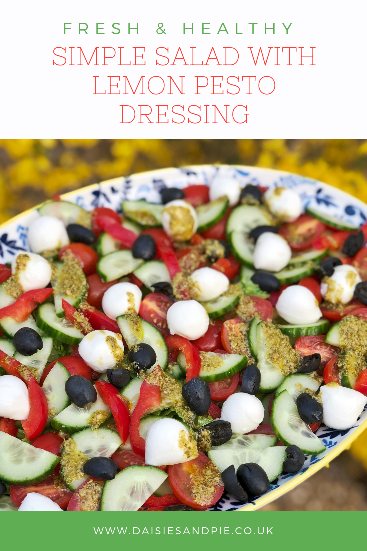 "a platter of salad with cos, cucumber, red peppers, baby plum tomatoes, black olives and mini mozzarella balls dressed wit lemony pesto dressing. Text overlay saying ""simple salad with lemony pesto dressing"""