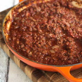 """orange cast iron casserole pan filled with oven baked bolognese sauce. Text overlay saying """"easy family dinner oven baked bolognese"""""""