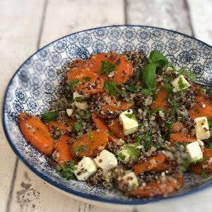 quinoa salad with roast carrots, feta cheese and herbs in a blue and white bowl.