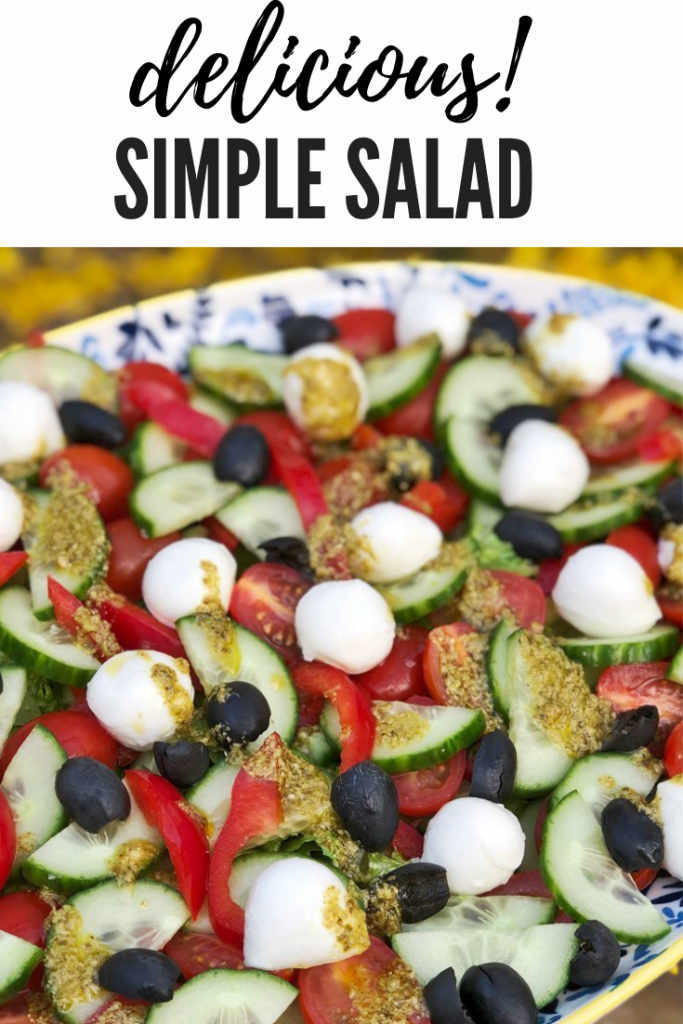 a platter of salad with cos, cucumber, red peppers, baby plum tomatoes, black olives and mini mozzarella balls dressed wit lemony pesto dressing. Text overlay saying 'delicious! simple salad'