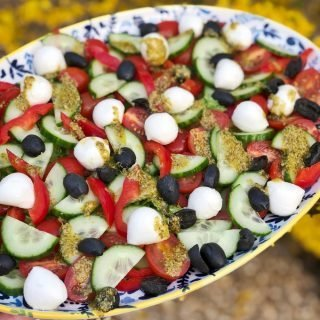 """a platter of salad with cos, cucumber, red peppers, baby plum tomatoes, black olives and mini mozzarella balls dressed wit lemony pesto dressing. Text overlay saying """"simple salad with lemony pesto dressing"""""""