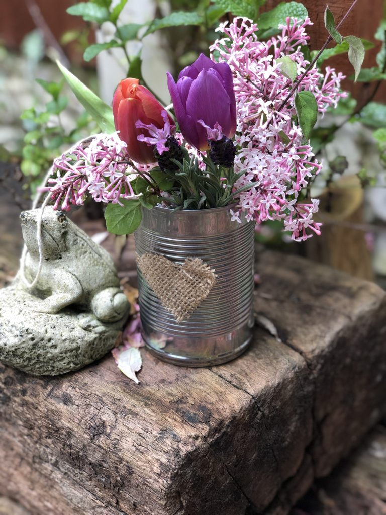DIY tin can May Day flower basket with string handle on the door step