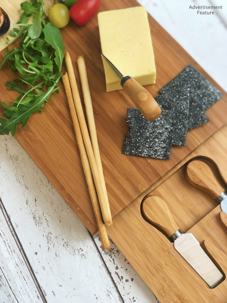 VonShef Bamboo cheeseboard with knives - charcoal crackers, cheddar cheese, breadsticks and rocket lying on the board