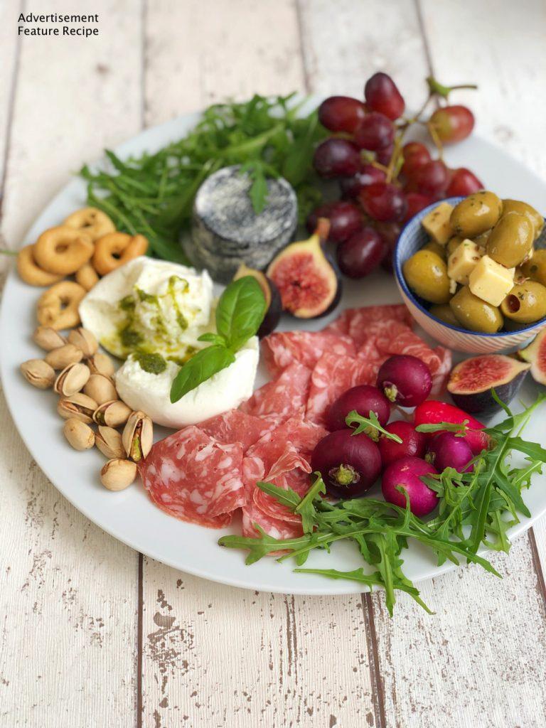Italian grazing platter with buffalo mozzarella, goats cheese, fruit and nuts.