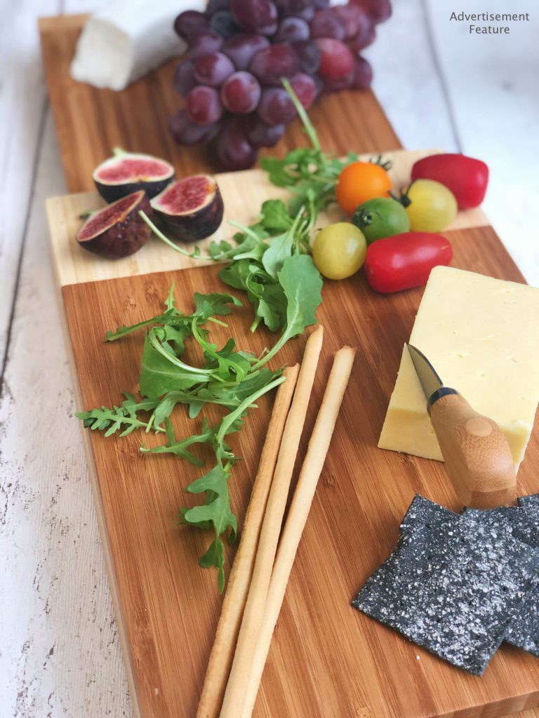VonShef bamboo cheeseboard with 3 tiers. Cheeseboard has on it charcoal crackers, breadsticks, heritage tomatoes, rocket, figs and grapes