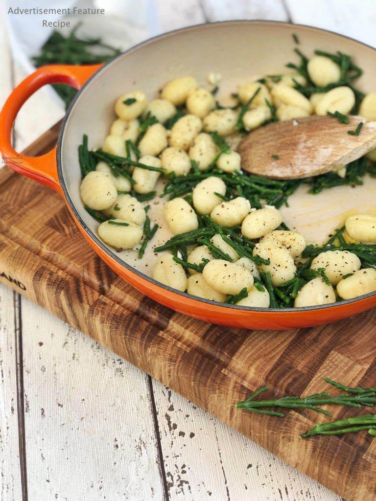 samphire with gnocchi and garlic butter in a a le creuset pan.