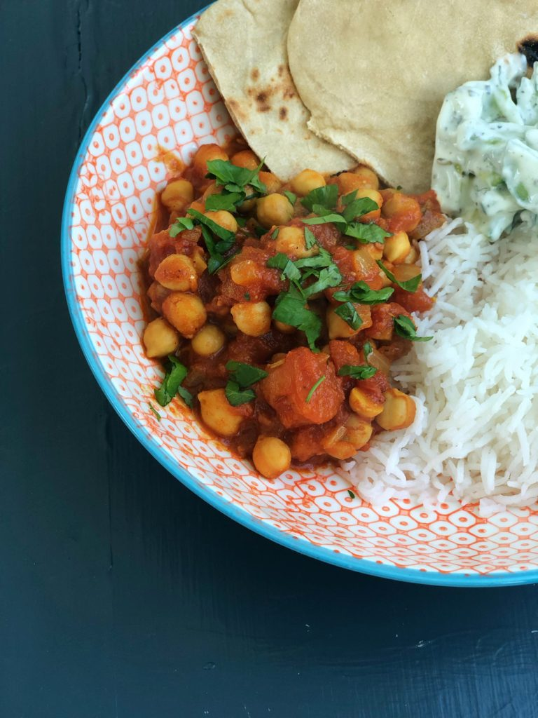Homemade vegan chickpea curry served with boiled rice, cucumber raita and homemade flatbreads