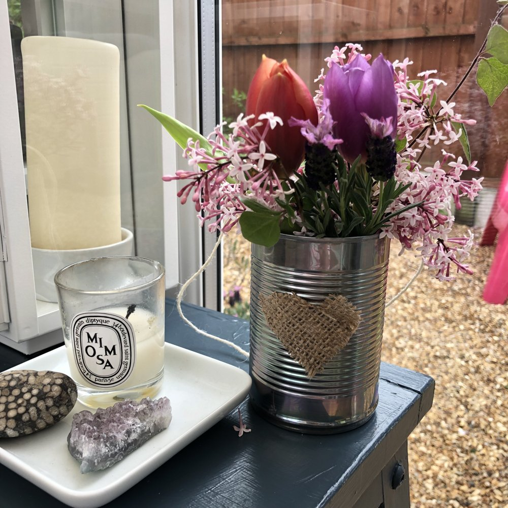 DIY tin can May Day flower basket with string handle on a dark grey painted table with Diptyque candle and amethyst crystal