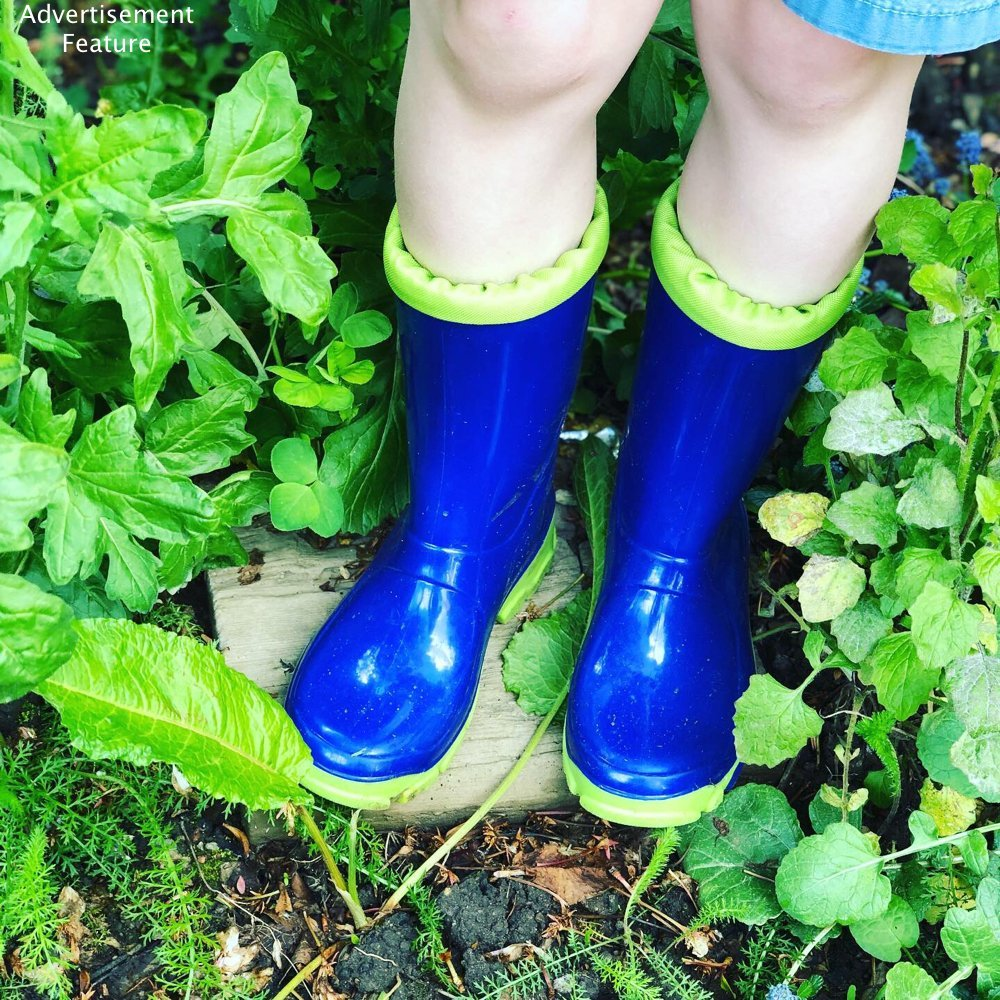 blue wellies in an overgrown garden