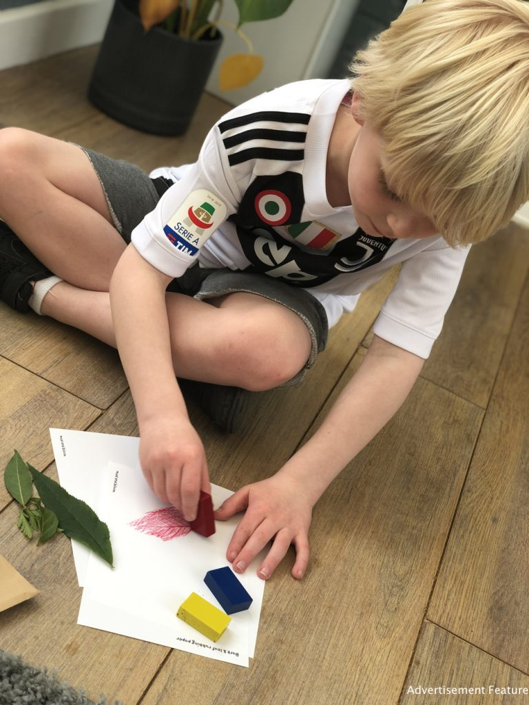 young boy doing leaf rubbings
