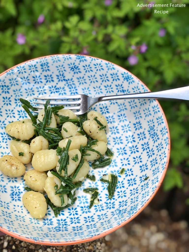 gnocchi with samphire and garlic butter in blue and white bowl