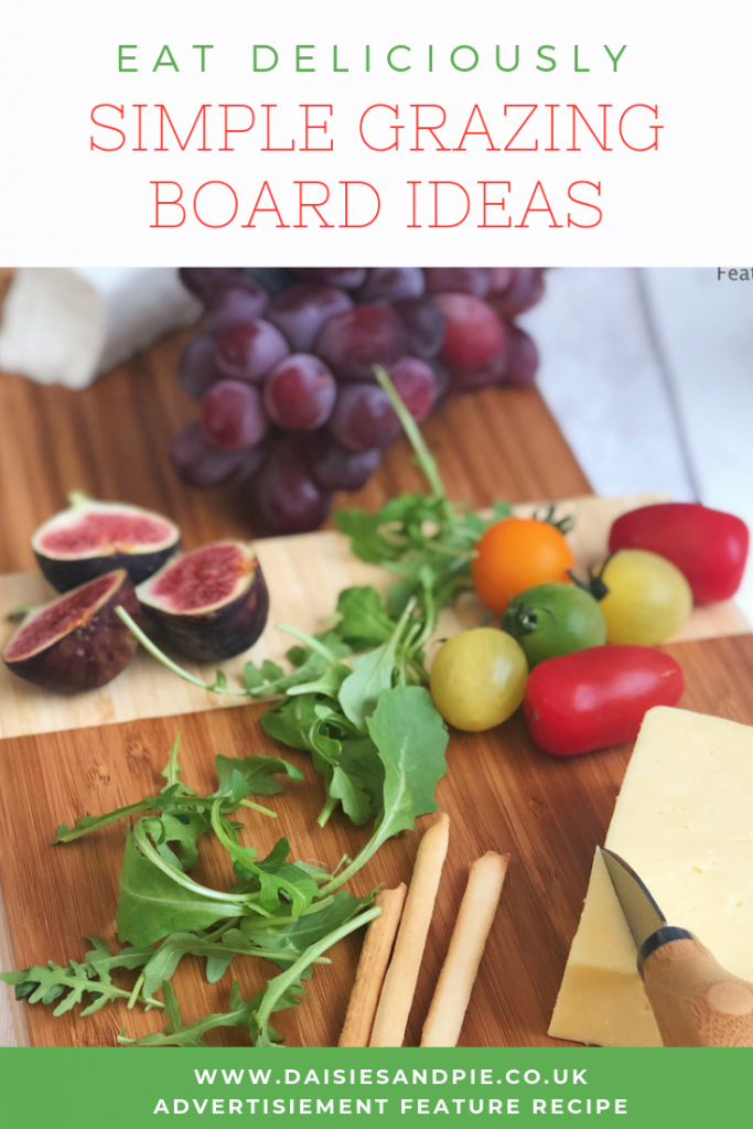 "VonShef bamboo cheeseboard with 3 tiers. Cheeseboard has on it charcoal crackers, breadsticks, heritage tomatoes, rocket, figs and grapes . Text overlay ""eat deliciously simple grazing board ideas"""