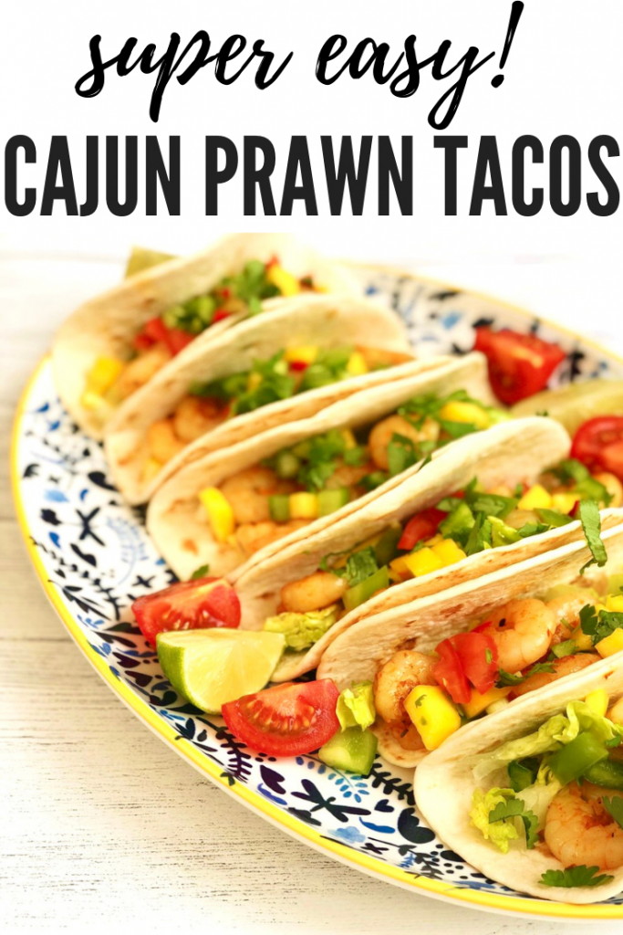 "prawn tacos made with cajun prawns and homemade mango salsa served on a blue and white serving plate with shredded lettuce and tomatoes. Text overlay ""super easy Cajun prawn tacos"""