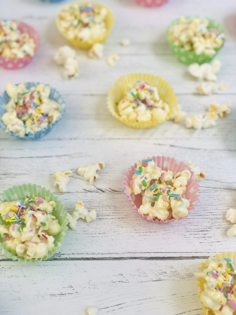 chocolate popcorn cupcakes with unicorn sprinkles in spotty paper cupcake cases