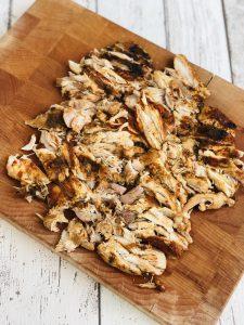 slow cooker shawarma chicken on wooden board.