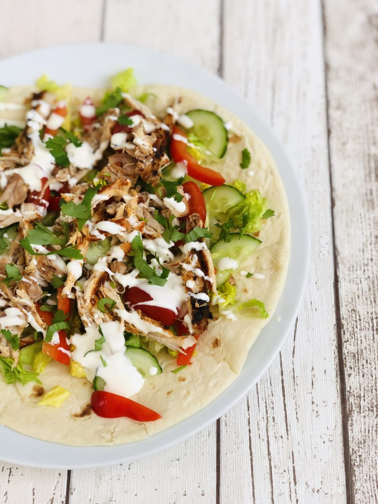 slow cooker shawarma chicken shredded and served with salad and yogurt dressing on a warmed flatbread.