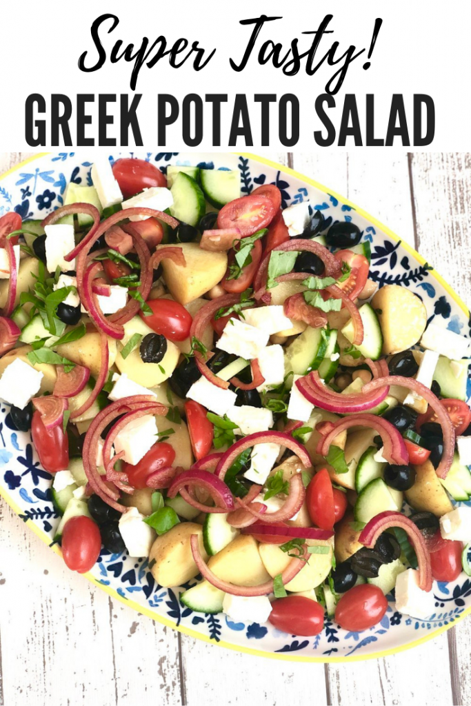 """platter of greek potato salad with feta cheese, baby tomatoes, cucumbers and olives. Text overlay """"super tasty Greek potato salad"""""""
