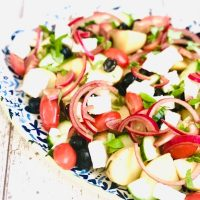 Greek potato salad with feta cheese, black olives, tomatoes, cucumbers and red onions served on a blue and white platter
