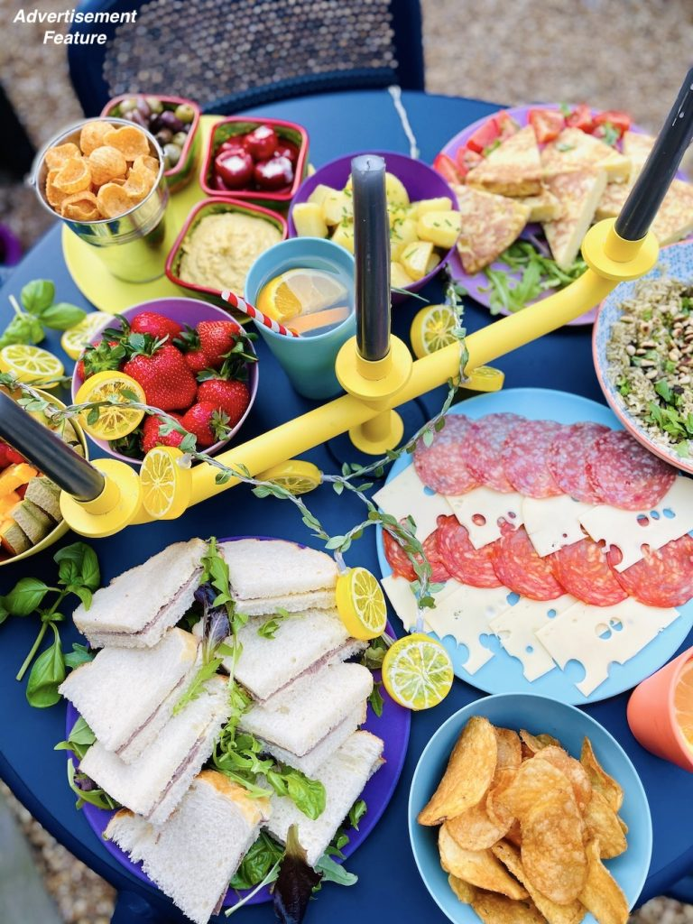 picnic food ideas spread across a table - platter of roast beef sandwiches, salami and cheese board, bowl of crisps, strawberries, hummus, rice salad