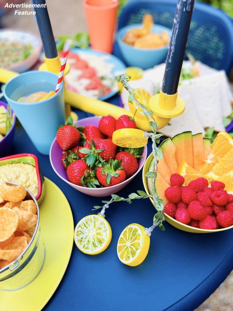 picnic food ideas - bowls of strawberries alongside a bowl of melon and orange slices with raspberries