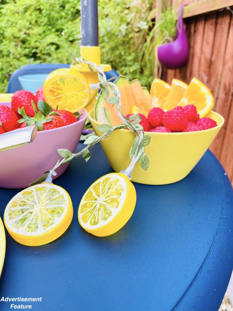 picnic food ideas - bowls of strawberries alongside a bowl of melon and orange slices with raspberries decorated with lemon slice fairy lights