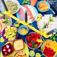 picnic food - boiled new potatoes, stuffed peppers, hummus and crisps, strawberries, melon and raspberries, rice salad, cheese and neat platter, sandwich platter
