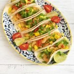 Homemade Cajun prawn tacos with spicy mango salsa garnished with lime wedges and tomatoes.