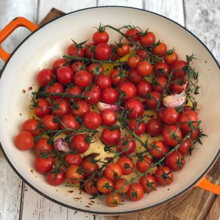 skillet filled with vine tomatoes and garlic ready to make roast tomato pasta sauce