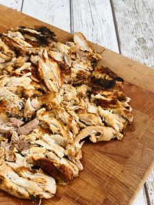 slow cooker shawarma chicken on wooden board.